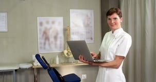 Fisioterapeuta de sexo femenino que usa el ordenador portátil almacen de video