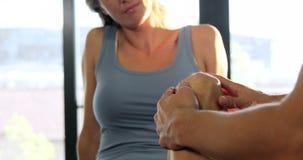 Fisioterapeuta de sexo masculino que da masaje de la rodilla al paciente femenino metrajes