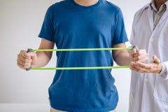 Fisioterapeuta do doutor que ajuda a um paciente masculino ao dar exercitando o tratamento em esticar seu braço com a faixa do ex fotografia de stock