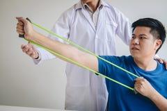 Fisioterapeuta do doutor que ajuda a um paciente masculino ao dar exercitando o tratamento em esticar seu bra?o com a faixa do ex foto de stock