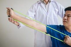Fisioterapeuta do doutor que ajuda a um paciente masculino ao dar exercitando o tratamento em esticar seu bra?o com a faixa do ex fotografia de stock royalty free