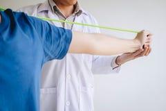 Fisioterapeuta do doutor que ajuda a um paciente masculino ao dar exercitando o tratamento em esticar seu bra?o com a faixa do ex foto de stock royalty free