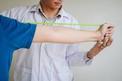 Fisioterapeuta do doutor que ajuda a um paciente masculino ao dar exercitando o tratamento em esticar seu bra?o com a faixa do ex fotos de stock