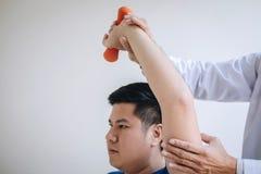 Fisioterapeuta do doutor que ajuda a um paciente masculino ao dar exercitando o tratamento em esticar seu bra?o com peso no foto de stock royalty free