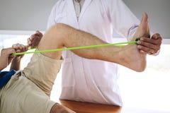 Fisioterapeuta do doutor que ajuda a um paciente masculino ao dar exercitando o tratamento em esticar seu pé na cama na clínica imagens de stock