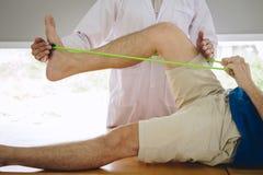 Fisioterapeuta do doutor que ajuda a um paciente masculino ao dar exercitando o tratamento em esticar seu p? na cama na cl?nica foto de stock royalty free