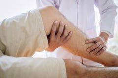 Fisioterapeuta do doutor que ajuda a um paciente masculino ao dar exercitando o tratamento que faz massagens o p? do paciente em  imagens de stock