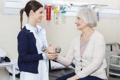 Fisioterapeuta fêmea Assisting Senior Woman para levantar pesos fotografia de stock