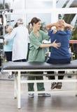 Fisioterapeuta fêmea de sorriso Assisting Senior Man em Exercisin fotografia de stock royalty free