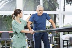 Fisioterapeuta fêmea Motivating Senior Patient a andar no meio imagem de stock royalty free