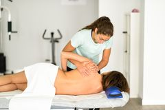 Fisioterapeuta fêmea profissional que dá a massagem do ombro à imagens de stock royalty free