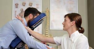 Fisioterapeuta fêmea que dá a massagem do braço a um paciente vídeos de arquivo