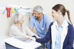 Fisioterapeuta With Female Patient e colega na reabilitação Cente fotografia de stock royalty free