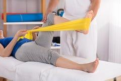 Fisioterapeuta Giving Leg Treatment con la banda del ejercicio foto de archivo