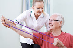 Fisioterapeuta Helping Senior Male para usar a faixa da resistência foto de stock royalty free