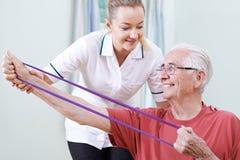 Fisioterapeuta Helping Senior Male para utilizar la banda de la resistencia Foto de archivo libre de regalías