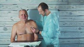 Fisioterapeuta joven que trabaja con el paciente mayor en clínica Examen del brazo dolorido almacen de video