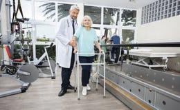 Fisioterapeuta masculino Helping Female Patient com caminhante Fotos de Stock Royalty Free