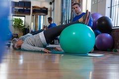 Fisioterapeuta que ajuda à mulher superior em executar o exercício na bola da aptidão fotografia de stock