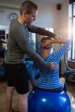 Fisioterapeuta que ajuda à mulher superior no exercício fotografia de stock