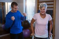 Fisioterapeuta que ajuda ao paciente superior da mulher a andar com quadro de passeio imagens de stock