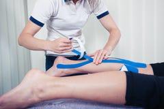 Fisioterapeuta que aplica la cinta del kinesio Fotos de archivo