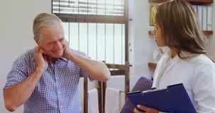 Fisioterapeuta que ayuda al hombre mayor mientras que consulta 4k metrajes