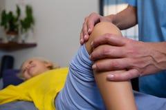 Fisioterapeuta que dá a fisioterapia à menina fotografia de stock