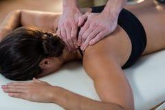 Fisioterapeuta que dá a fisioterapia ao pescoço de um paciente fêmea foto de stock
