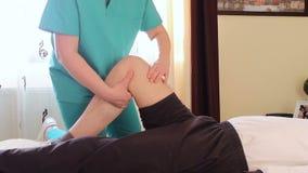 Fisioterapeuta que dá uma massagem do joelho vídeos de arquivo