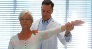 Fisioterapeuta que da masaje de la mano a la mujer mayor almacen de video
