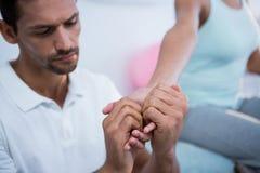 Fisioterapeuta que da masaje de la mano a una mujer Fotos de archivo libres de regalías