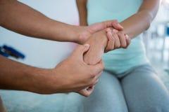 Fisioterapeuta que da masaje de la mano a una mujer Imagen de archivo