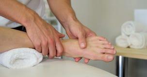 Fisioterapeuta que da masaje del pie a un paciente femenino metrajes