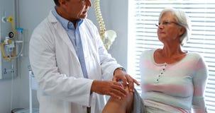 Fisioterapeuta que da terapia de la rodilla a la mujer mayor almacen de video