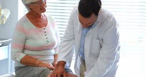 Fisioterapeuta que da terapia de la rodilla a la mujer mayor almacen de metraje de vídeo