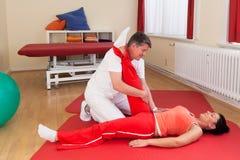 Fisioterapeuta que exercita com paciente Fotos de Stock