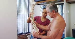 Fisioterapeuta que explica el modelo de la espina dorsal al paciente mayor 4k almacen de video