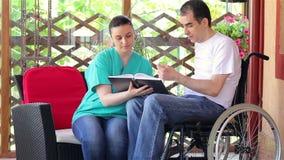 Fisioterapeuta que explica exercícios ao homem novo na cadeira de rodas vídeos de arquivo