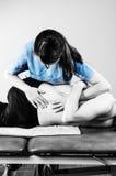 Fisioterapeuta que faz a manipulação para equipar o paciente na silhueta Fotografia de Stock Royalty Free