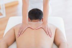 Fisioterapeuta que faz a massagem traseira a seu paciente foto de stock
