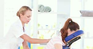 Fisioterapeuta que faz a massagem traseira a seu paciente vídeos de arquivo
