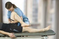 Fisioterapeuta que hace estirar de las piernas del paciente del hombre osteopathy fotos de archivo