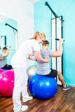 Fisioterapeuta que hace la rehabilitación del deporte con el paciente Foto de archivo libre de regalías