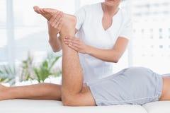 Fisioterapeuta que hace masaje de la pierna a su paciente Imagenes de archivo