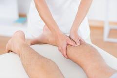 Fisioterapeuta que hace masaje del becerro a su paciente Imagen de archivo