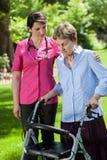 Fisioterapeuta que mira a la mujer que usa al caminante ortopédico Fotos de archivo