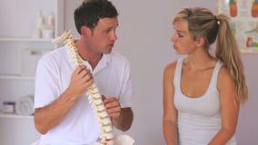 Fisioterapeuta que muestra a su paciente un modelo de la espina dorsal metrajes