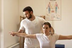 Fisioterapeuta que pratica com paciente imagens de stock