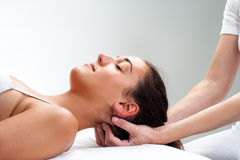 Fisioterapeuta que pressiona para trás da cabeça da mulher